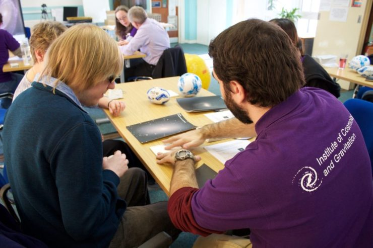 A photo from the Tactile Universe community event in January 2017 showing four people sitting around a table. The person in the front is explaining a tactile galaxy to the person on the left.