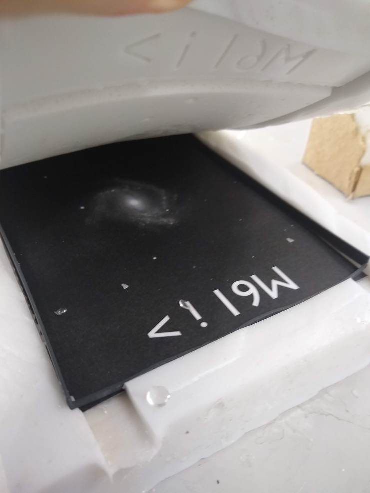 The silicone mould for M61 being held open. Inside the mould is the black and white galaxy image and a plastic frame holding the image in place.